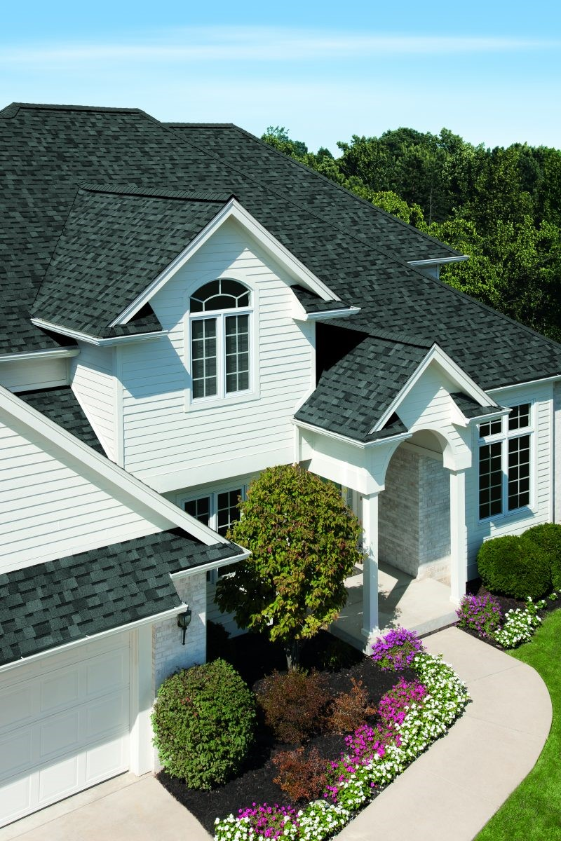 A white house with a contrasting black shingle roof.