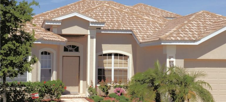 A ground view of a newly installed tan tile roof.