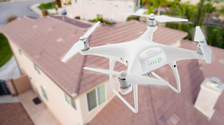 A drone used for drone roof inspections hovering over a roof.
