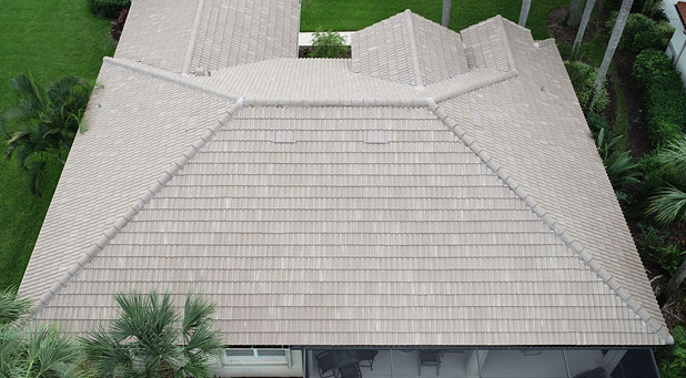 A top-down view of a house with a newly installed tan tile roof.