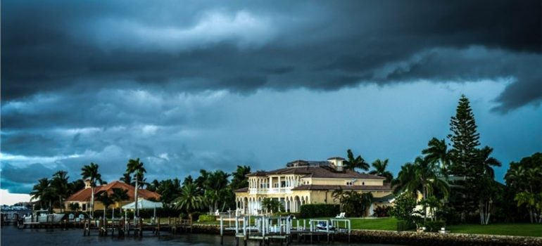 Storm clouds above two houses with large roofs.