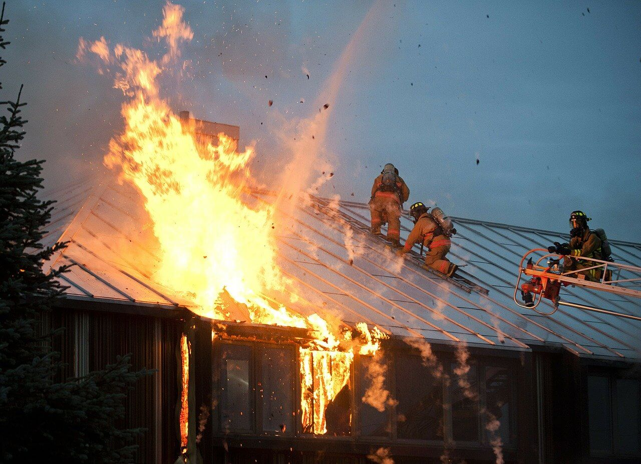 Firefighters climbing on a metal roof to put our a blazing fire.